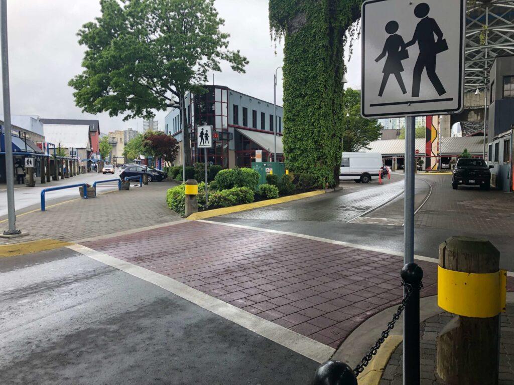 decorative crosswalk with stamped asphalt at granville island brewery crosswalk sign